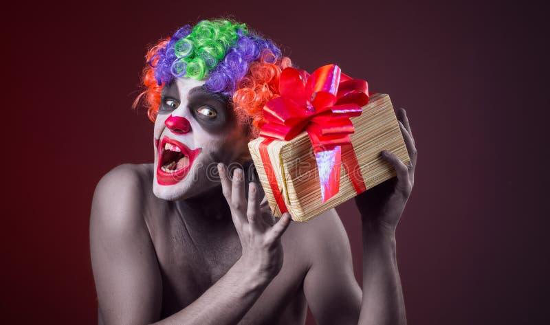 Furchtsames Clownmake-up und mit einem schrecklichen Geschenk stockbild