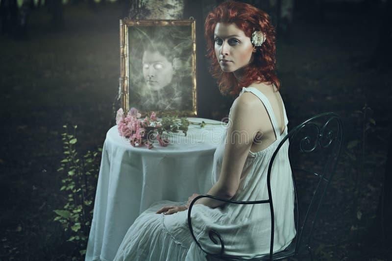 Furchtsames Geistgesicht im dunklen Spiegel lizenzfreie stockbilder