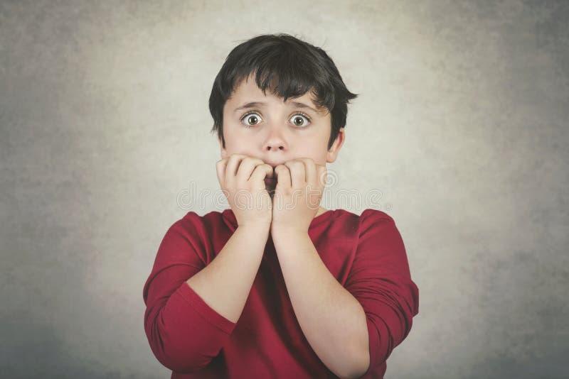 Furchtsames Kind, das seine Fingernägel beißt stockbild