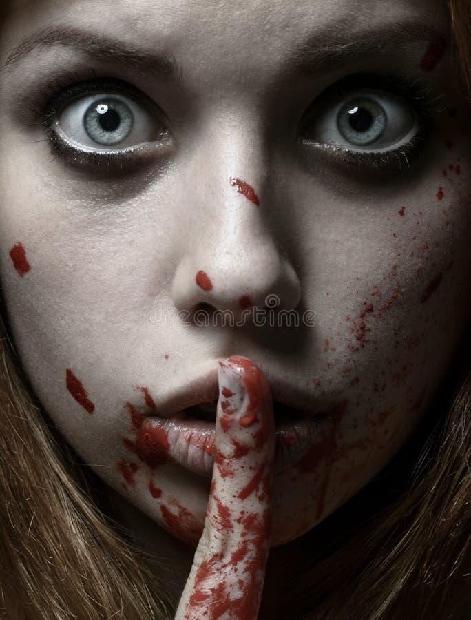 Furchtsames Mädchen- und Halloween-Thema: Porträt eines verrückten Mädchens mit einem blutigen Gesicht im Studio lizenzfreie stockfotografie