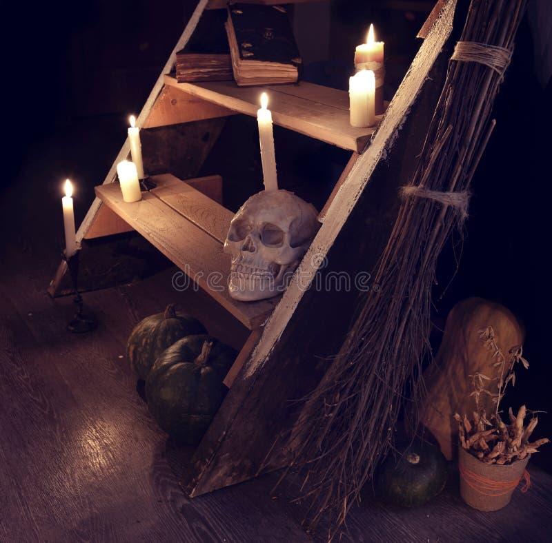 Furchtsames Stillleben mit dem Schädel, den Kerzen und schlechtem Treppenhaus im Hexenhaus lizenzfreie stockfotografie