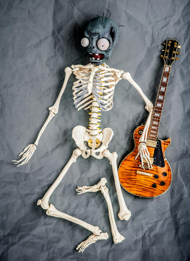 Furchtsames weißes Skelett, das nahe auf grauem Hintergrund liegt stockbild