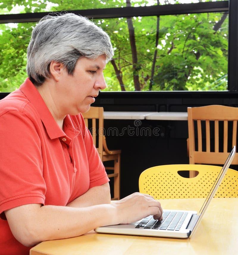 Furetage posé par femme entre deux âges sur l'ordinateur portatif photo stock
