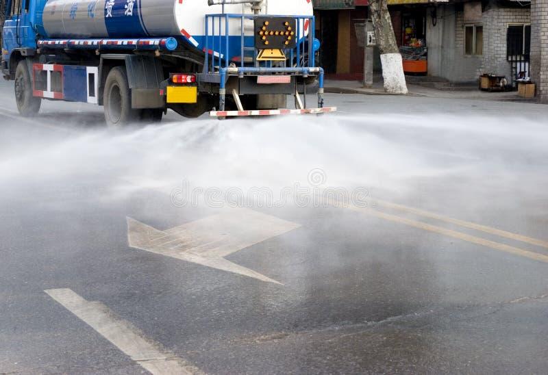 Furgone dell'acqua che innaffia la strada fotografie stock libere da diritti
