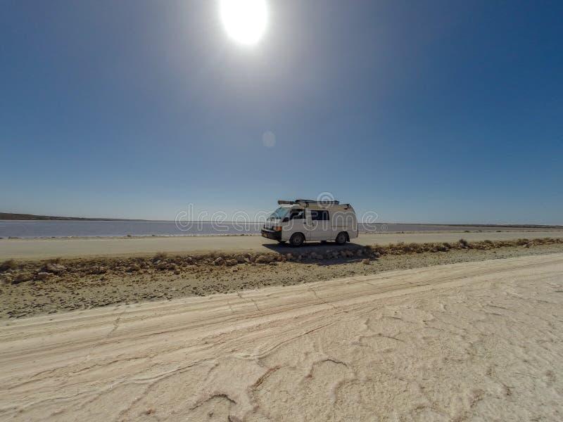 furgone su una strada diritta della ghiaia fra 2 laghi di sale nel dessert di nullabor dell'Australia, Australia Meridionale, Aus fotografia stock