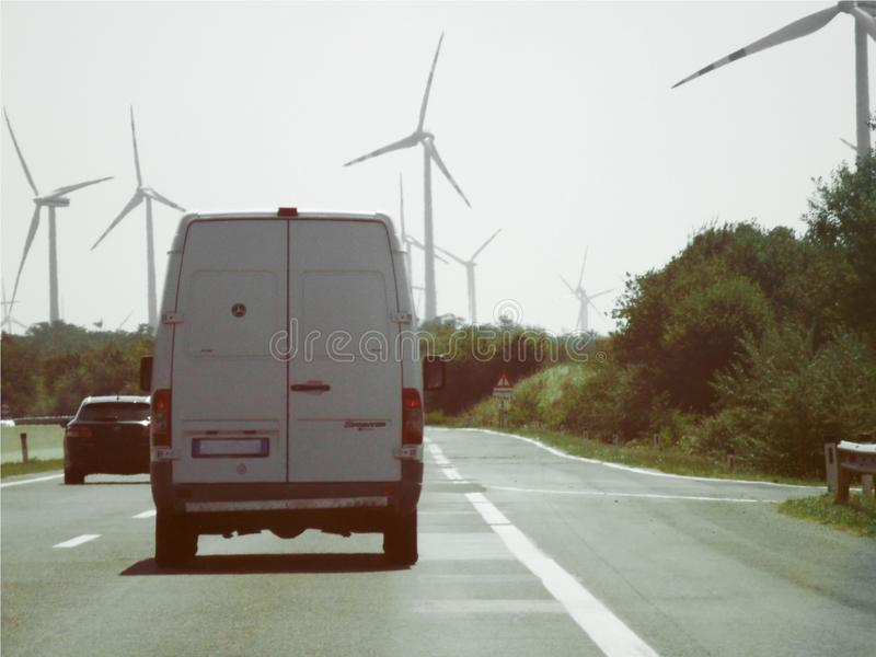 Furgoneta blanca en un camino cerca de un parque eólico, polos grandes del viento que producen electricidad renovable foto de archivo libre de regalías