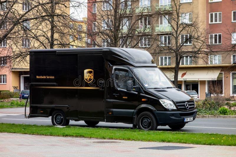 Furgoneta de Mercedes-Benz Sprinter del marrón de la arca en una calle que entrega un paquete imagen de archivo libre de regalías