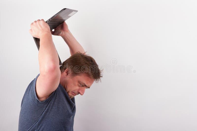 Furioous man smashing his laptop stock photos