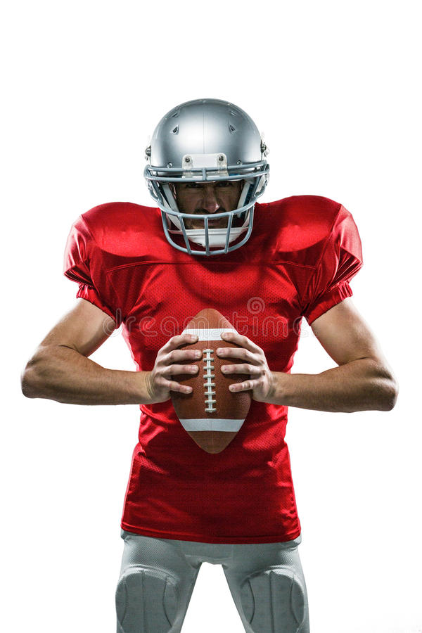 Furious American football player in red jersey and helmet holding ball. Portrait of furious American football player in red jersey and helmet holding ball on royalty free stock photo
