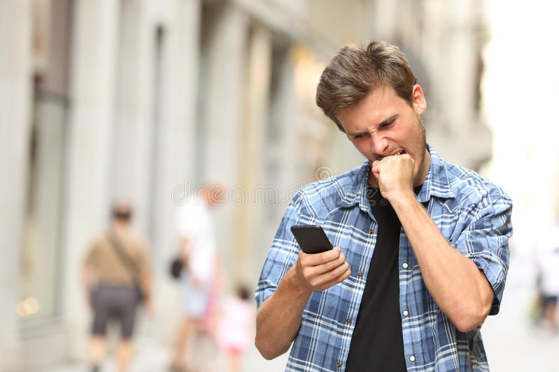Furious angry man watching mobile phone. Furious angry man watching apps in the mobile phone in the street royalty free stock photo