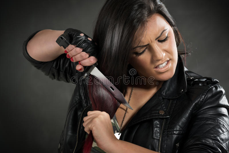 Furious Army girl. Young anger military woman holding bayonet and wants to cut hair stock image