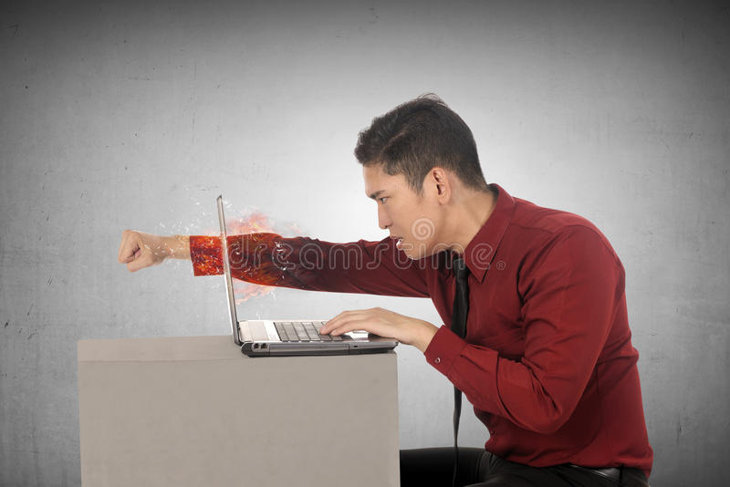 Furious asian business man throws a punch into the laptop. On grey background stock image