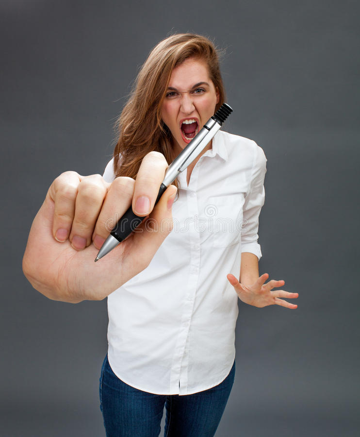 Furious beautiful young woman shouting and threatening in holding pen. Furious beautiful young woman shouting in holding a big pen in the foreground, threatening stock photo