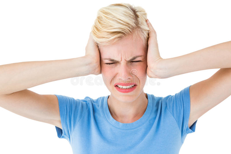 Furious blonde woman holding her head. On white background royalty free stock image
