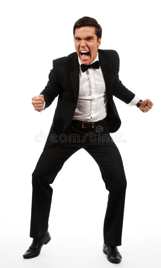 Furious business man. Furious adult yelling and holding his fists ready to fight, sanding and wearing formal clothes royalty free stock photos