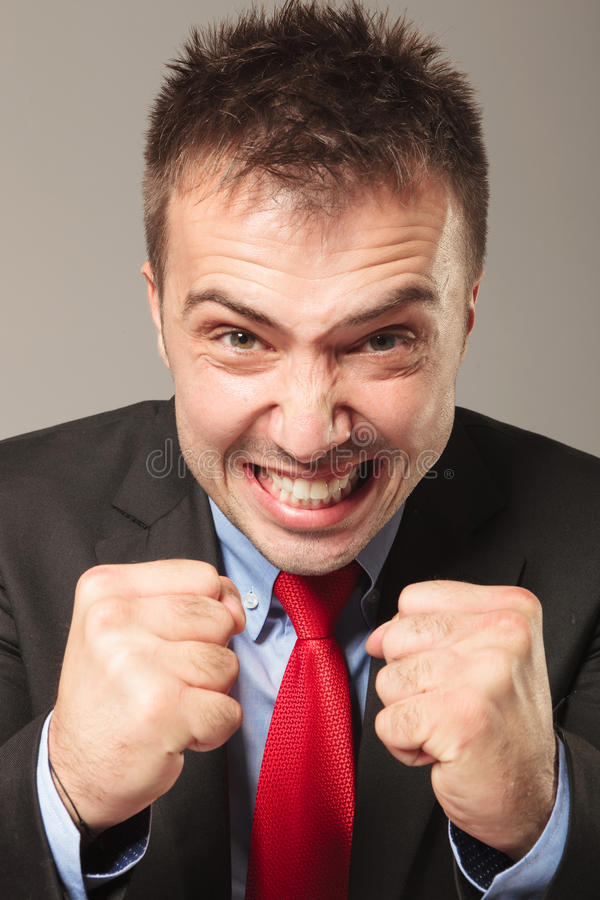 Furious business man making a angry face. While showing you his fists stock photos