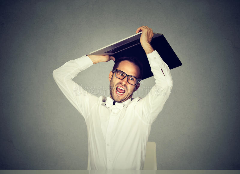 Furious business man about to smash throw his laptop computer. Furious nervous business man about to smash throw his laptop computer stock photos
