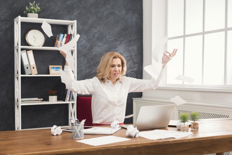 Furious business woman throwing working documents at office desktop. Angry business woman throwing and tearing working documents at wooden office desk, copy royalty free stock images