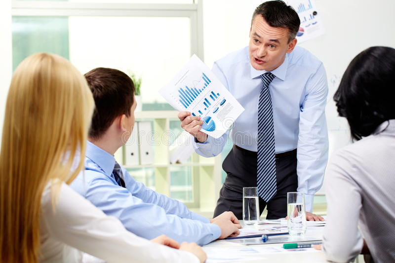 Furious businessman. Business worker showing charts and graphs to his employees with a furious look royalty free stock photography