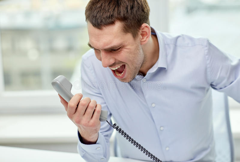 Furious businessman calling on phone in office. Business, people, emotions, stress and communication concept - furious businessman calling on phone in office stock photos