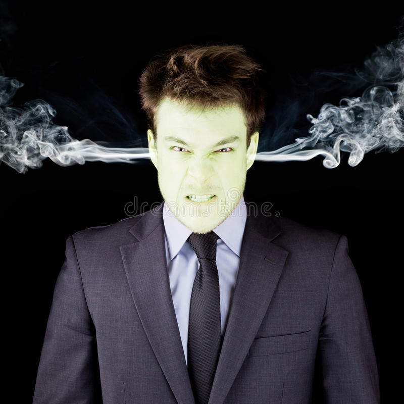 Furious businessman getting green face. Furious businessman getting green isolated on black royalty free stock images