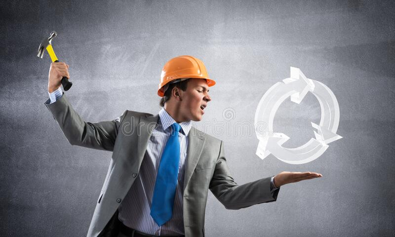 Furious businessman going to crash recycle sign. Furious businessman going to crash glass recycle sign with hammer. Young handsome man in business suit and stock image