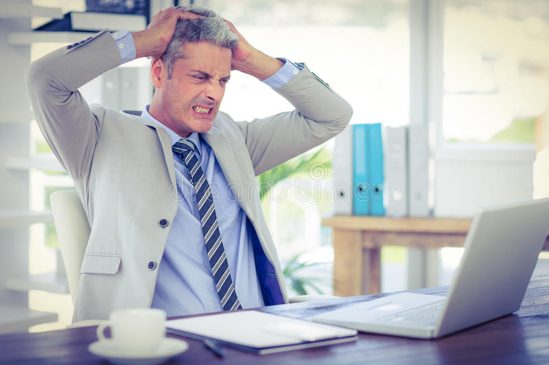 Furious businessman looking at laptop computer. In office royalty free stock photography