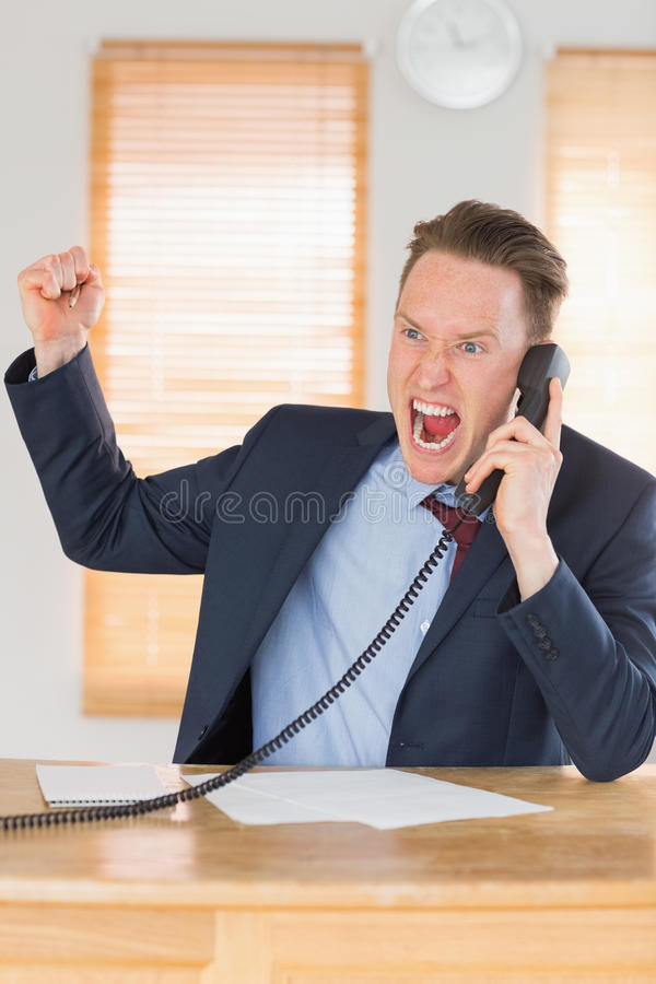 Furious businessman outraged on the phone. In his office stock image