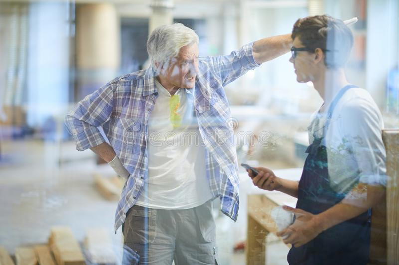 Furious carpenter foreman yelling at lazy worker royalty free stock photo