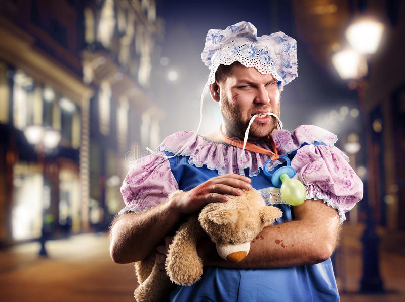 Furious chav man on street at night. Furious chav man weared as baby on street at night stock images