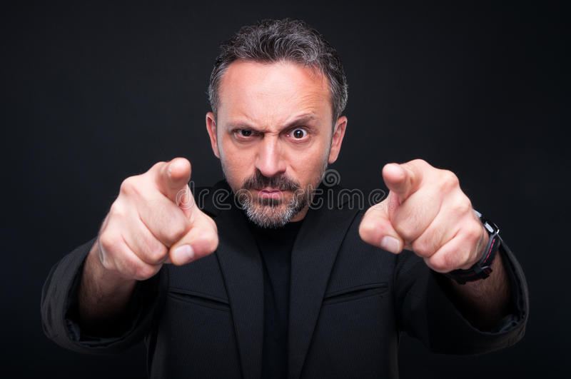 Furious classy man pointing at you. With both index fingers on dark background royalty free stock photography