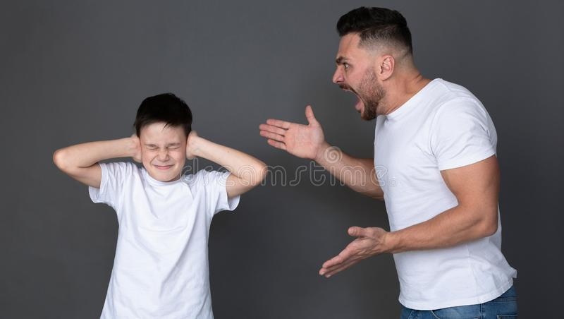 Furious dad screaming at his son, scared child close his eyes and ears stock photography