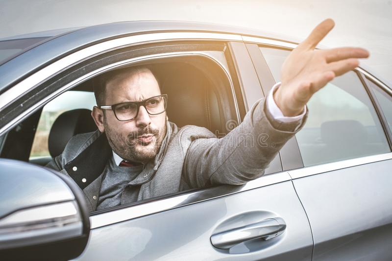 Furious driver. Enraged male driver shouts and gestures threateningly stock images
