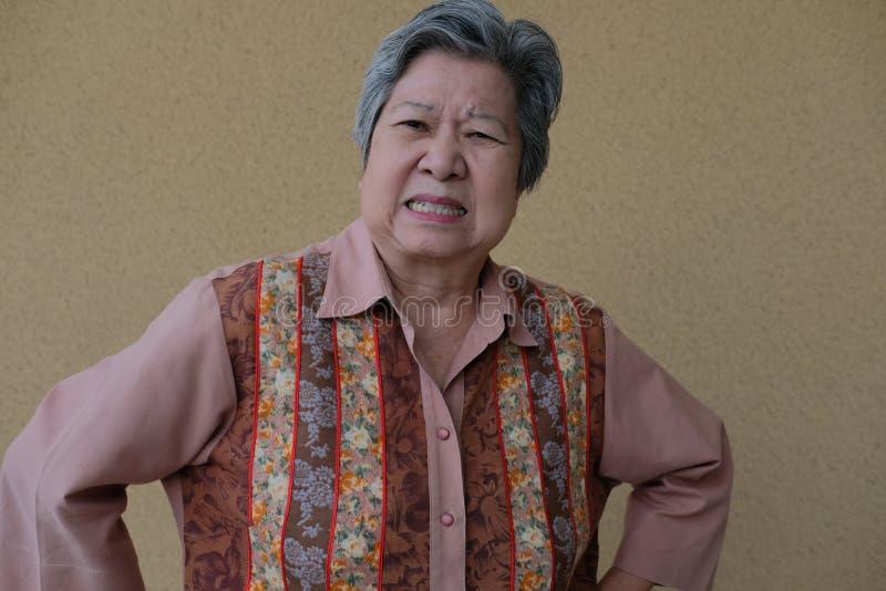 Furious elder woman. enraged elderly female. angry asian senior. Portrait of furious elder woman. enraged elderly female. angry asian senior royalty free stock image