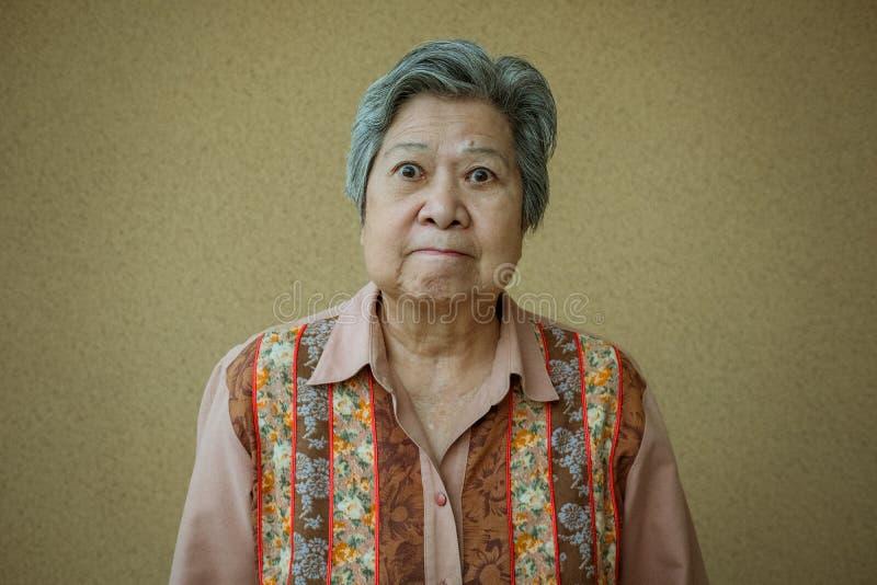 Furious elder woman. enraged elderly female. angry asian senior. Portrait of furious elder woman. enraged elderly female. angry asian senior royalty free stock photos
