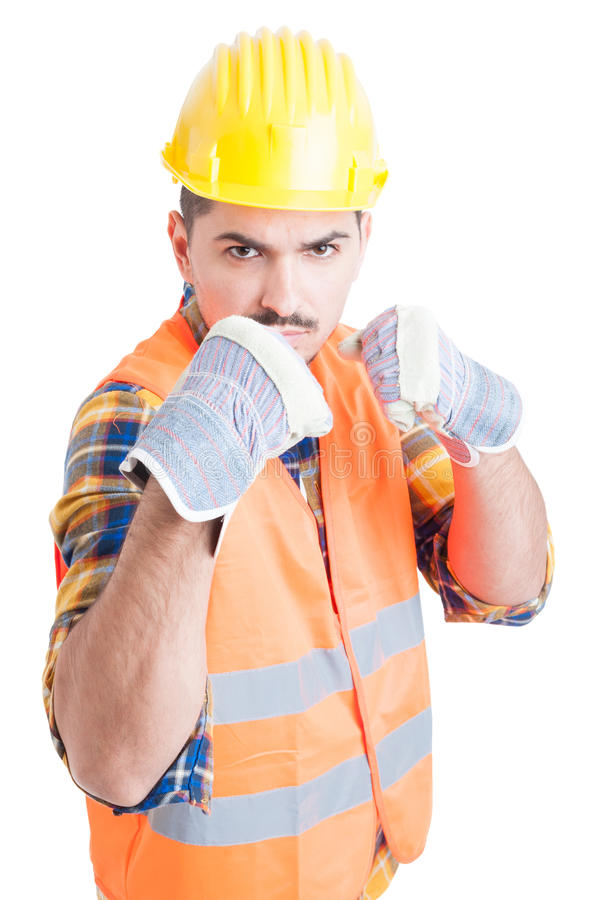 Furious engineer showing his fists and standing in fighting position. With bad attitude on his face isolated on white stock photography
