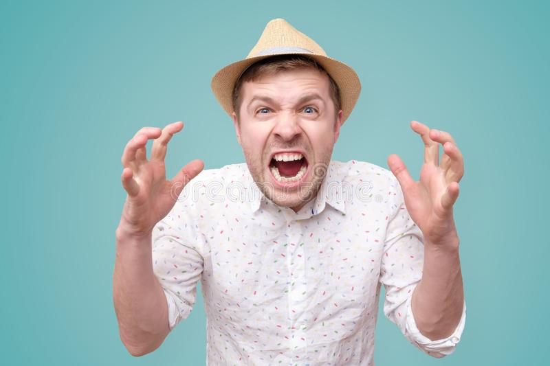 Furious,enraged man with mouth opened in shout. Show level of his anger, isolated over blue background royalty free stock image