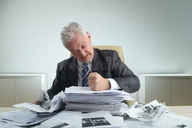 Furious Entrepreneur Crumpling Documents. Waist-up portrait of furious aged entrepreneur wearing classical suit crumpling documents while relieving stress at royalty free stock image