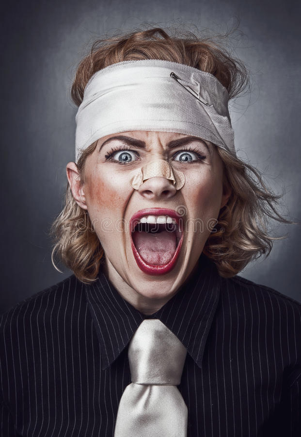 Furious face. Of injured woman with bandage on head screaming stock photo