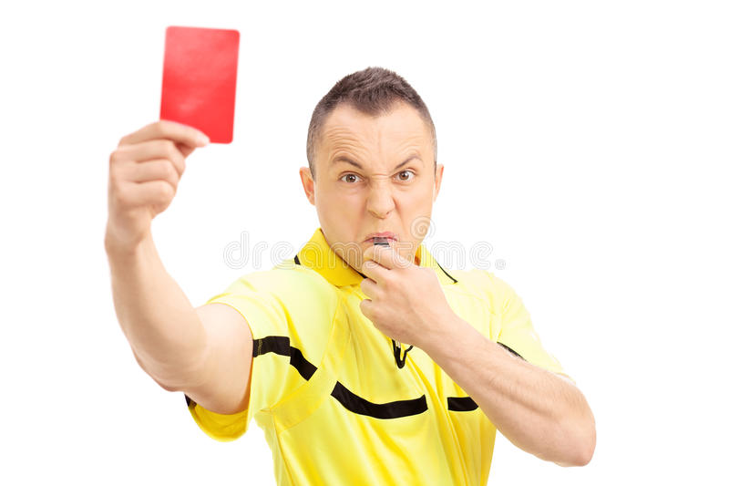 Furious football referee showing a red card. And blowing a whistle isolated on white background stock image