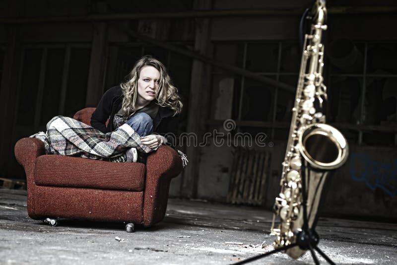 Furious girl starring at saxophone stock photo