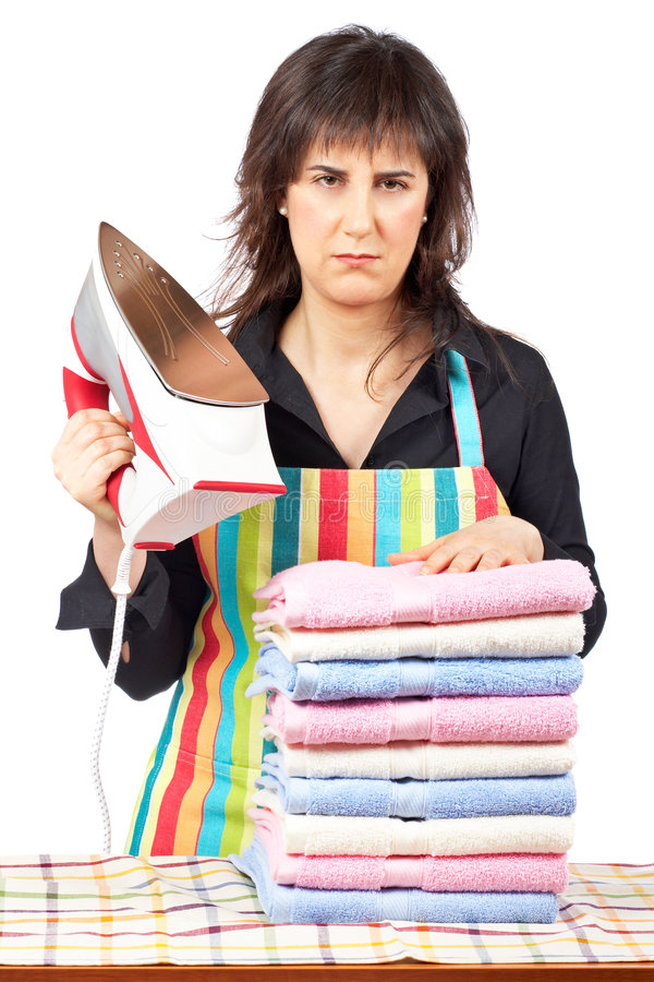 Furious housewife. In apron holding a eletric iron close to towels stacked stock images