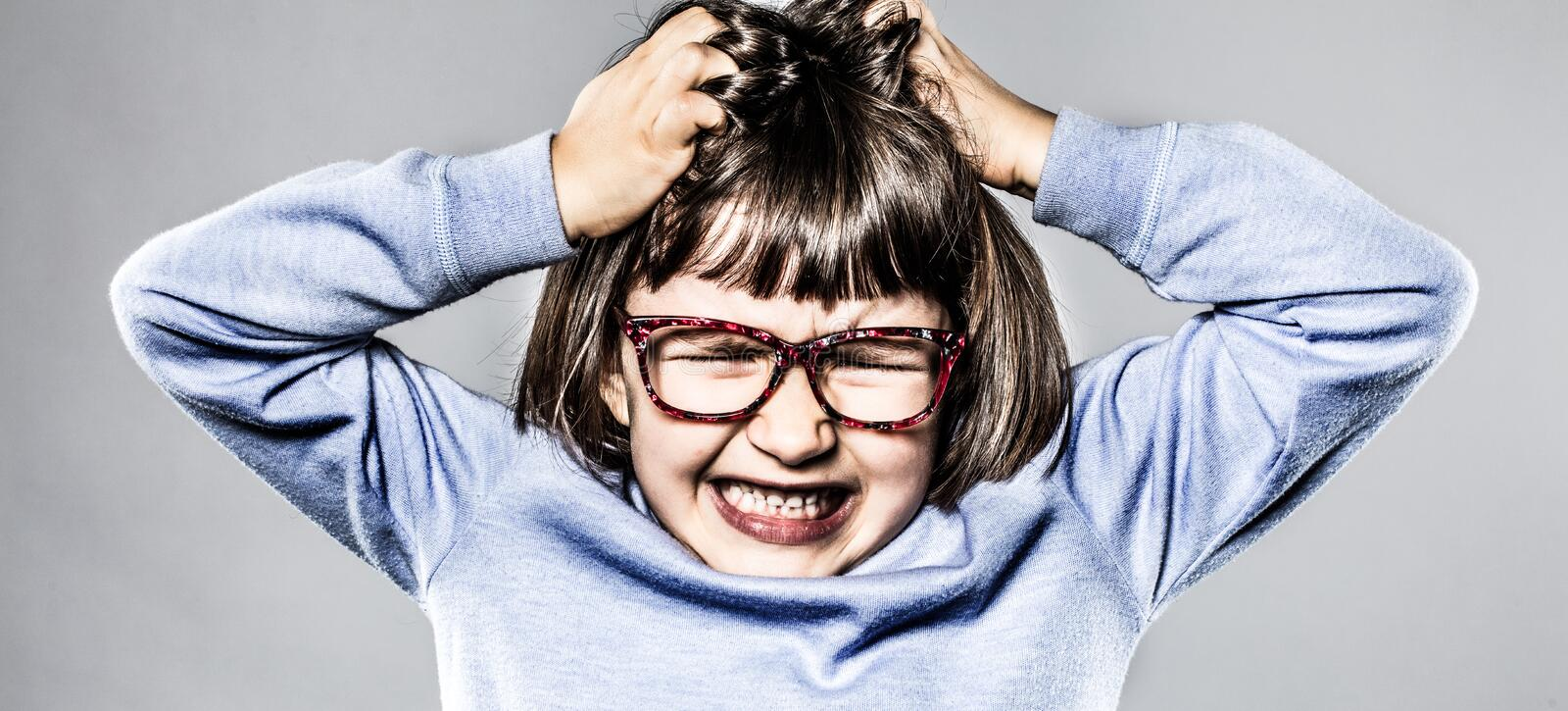 Furious kid having tantrum, scratching head for anger and frustration royalty free stock photography
