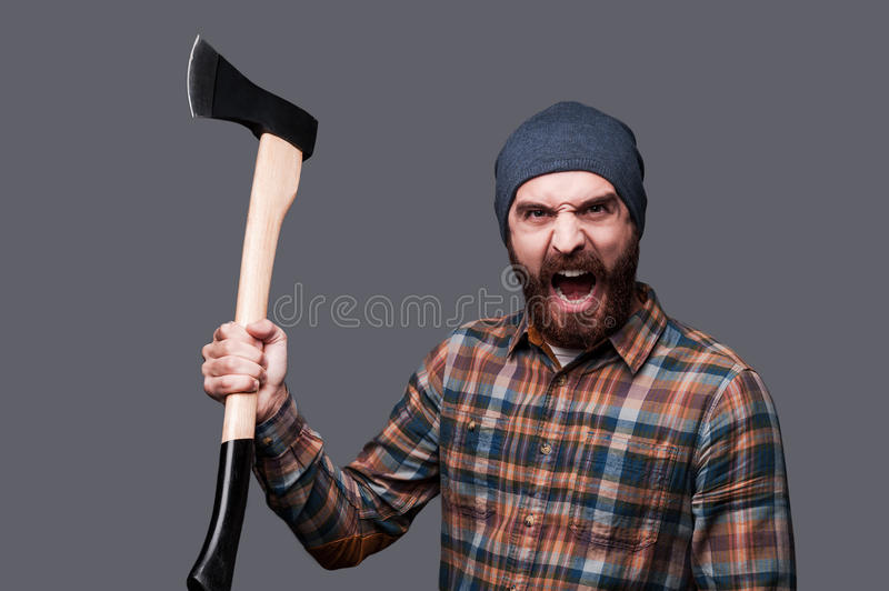 Furious lumberjack. Furious young bearded man swinging his axe and shouting while standing against grey background stock photo
