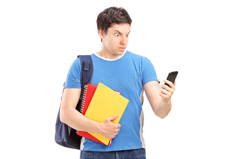 Furious male student looking at his phone. Isolated on white background stock images