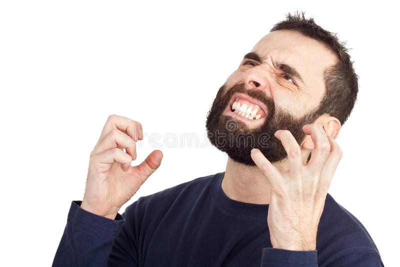 Furious man. A furious bearded man rising his hands in anger and showing his teeth in the process. Isolated against a white background royalty free stock image