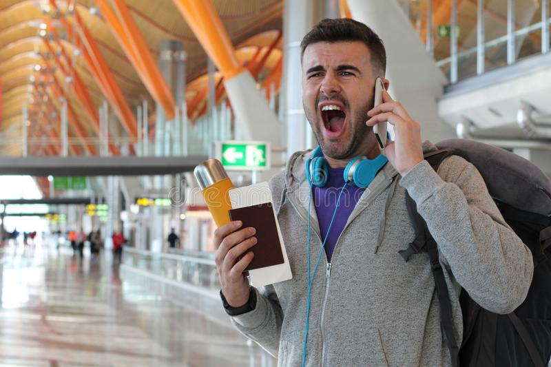 Furious man getting a call at the airport.  stock images