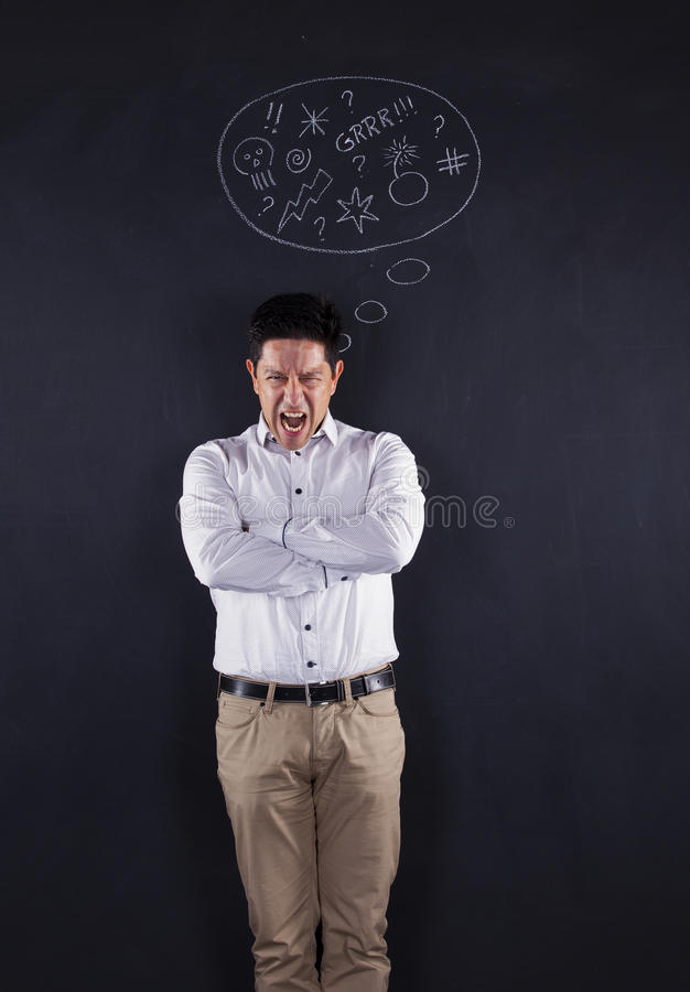Furious man. Next to a chalkboard showing his emotions stock photography