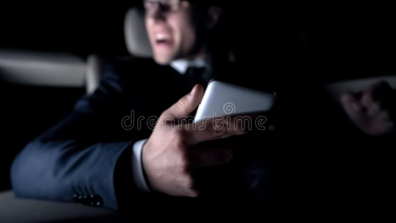 Furious man shouting in car, got message about failed contract, work problems stock photography