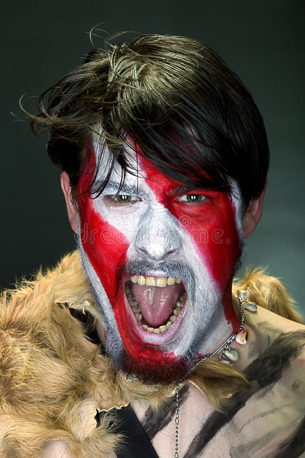 Furious man. Studio portrait of a man in war paint on a dark background, furiously screaming, the barbarian of ancient times, Viking and savage stock photography